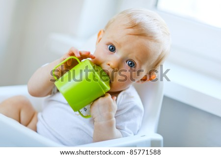 Lovely baby  sitting in chair and drinking from baby cup - stock photo