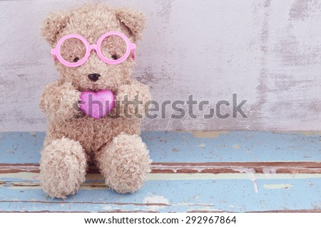 lovely bear doll wearing pink glasses and holding pink heart shape - stock photo