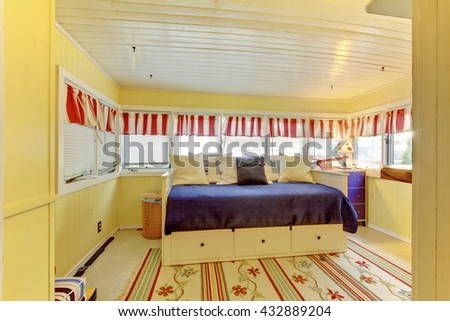 Lovely bed with blue bedding and nightstand in small bright bedroom with carpet windows. - stock photo
