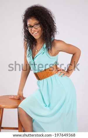 Lovely  black girl, together with  a wooden stool and looking at the camera with a  pleasing smile
