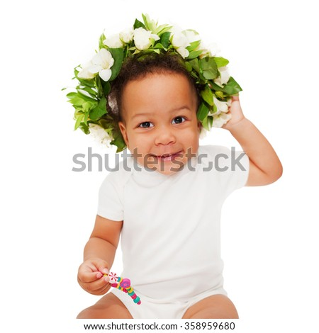 Lovely black mulatto baby with floral wreath on her head. Isolated on white background
