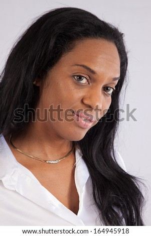 Lovely black woman in a white, silk blouse,  sitting and looking at the camera with a pleasing expression