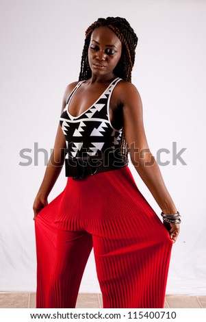 Lovely black woman in red pants, holding her pants out and looking at the camera with a friendly, thoughtful  expression - stock photo