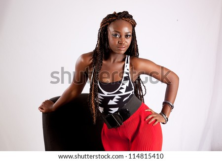 Lovely black woman in red slacks kneeling in a black business chair with one hand on her hip and the other on the back of the chair and looking at the camera with a thoughtful, friendly expression - stock photo