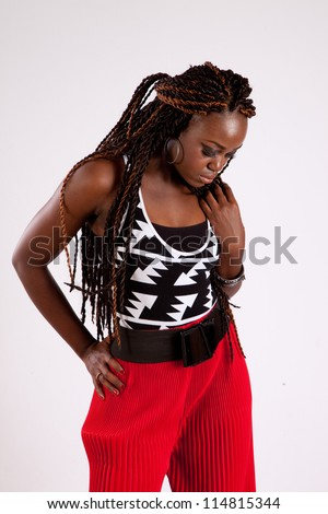 Lovely black woman in red slacks, looking down with a serious, thoughtful look, with on hand on her hip and the other on her shoulder - stock photo