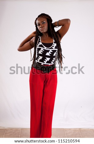 Lovely black woman in red slacks, standing with her hands behind her head and looking at the camera with a thoughtful expression - stock photo