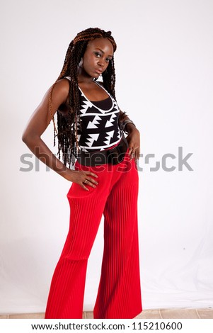 Lovely black woman in red slacks, standing with her hands on her hips and looking at the camera with a thoughtful expression - stock photo