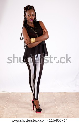 Lovely black woman in striped pants, standing with her arms folded and a pensive expression - stock photo