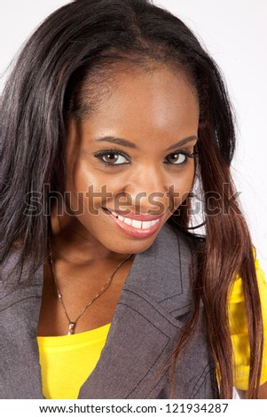 Lovely black woman in yellow shirt and black vest, with eye contact to the camera and a thoughtful, friendly expression