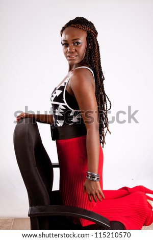 Lovely black woman kneeling backwards in a chair and resting her hand on the back of the chair while she looks at the camera with a playful expression - stock photo