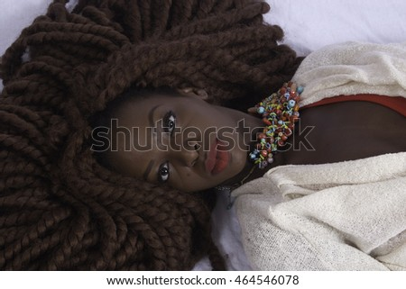 Lovely black woman thoughtfully reclining
