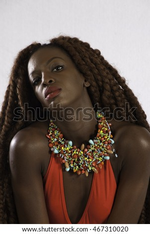 Lovely black woman with long dreadlocks, looking thoughtfully at the camera