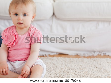 Lovely blond baby looking at the camera while sitting on a carpet in the living room - stock photo