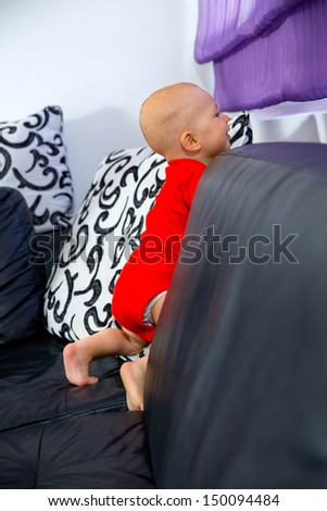 Lovely blond baby standing on a sofa in the living room - stock photo