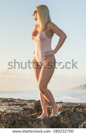 lovely blond female model in tight pink ballet swimsuit at beach - stock photo