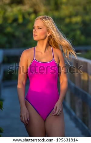 lovely blond female swimsuit model along florida beach boardwalk path with morning sunlight - stock photo