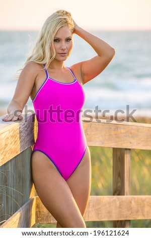 lovely blond female swimsuit model poses at florida atlantic beach at sunrise in one-piece suit - stock photo