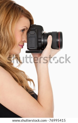 Lovely blond-haired woman taking a photo with a camera on a white background