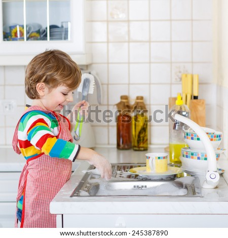 Lovely blond kid boy washing dishes in domestic kitchen. Child having fun with helping his parents with housework. Indoors, kid in colorful clothes. - stock photo
