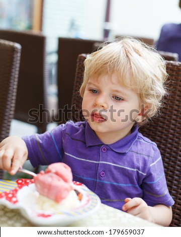 Lovely blond little boy eating ice-cream in city cafe in summer.