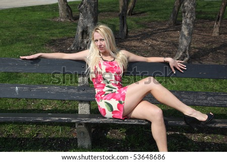Lovely blond relaxing on a park bench