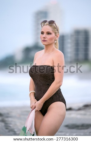 lovely blonde female in one piece swimsuit at beach on clouding morning - stock photo