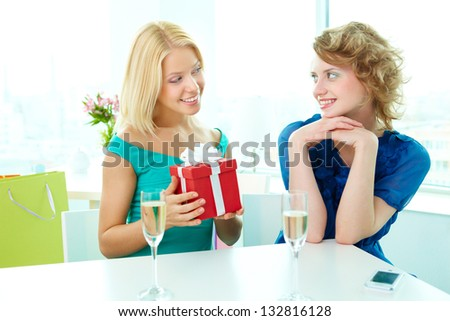Lovely blonde giving a present to her friend - stock photo
