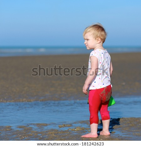 Lovely blonde little toddler girl in colorful outfit plays with watering can at a shore of the sea on a long calm peaceful beach on a warm sunny summer day