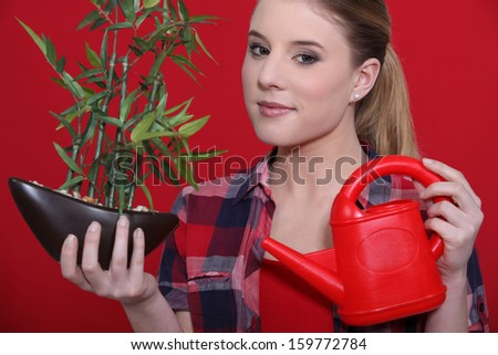 lovely blonde watering plant against red background - stock photo