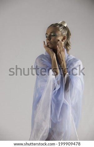 Lovely blonde woman with minimal makeup posing with her hands to her face with blue and white organza draped around her