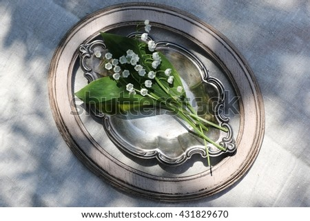 Lovely bouquet of lilies of the valley on the very old vintage dish in beige oval wooden frame. Natural light and shadows. Grey linen background. Sunny summer day in the garden