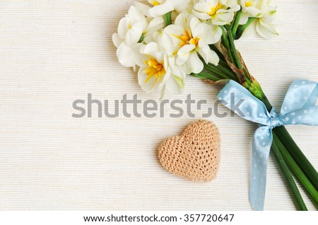 lovely bouquet of narcissus with a charming blue bow and knitting heart on beige cotton