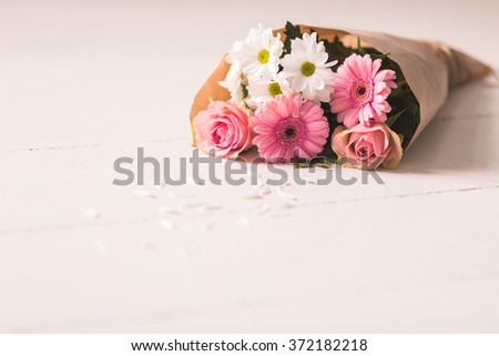 Lovely bouquet wrapped in paper and flower petals around - stock photo