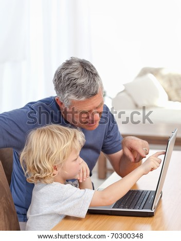 Lovely boy and his grandfather looking at their laptop at home - stock photo