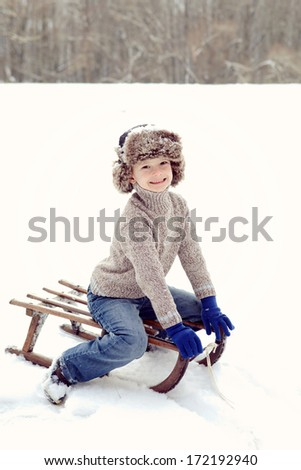 Lovely boy having fun on ancient sledge on winter snow day - stock photo