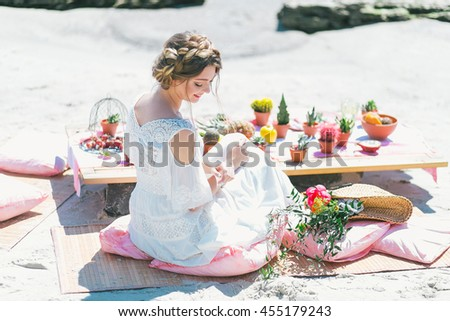 Lovely bride having breakfast by the sea.