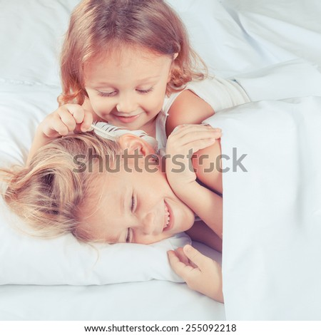 Lovely brother and sister lying in bed at home. Concept of Brother And Sister Together Forever - stock photo
