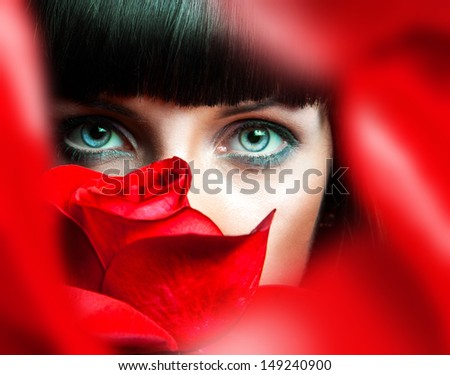 Lovely brunette behind red rose in studio - stock photo