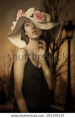lovely brunette female with romantic spring style, posing with black dress and big flowers hat with colorful roses.  - stock photo