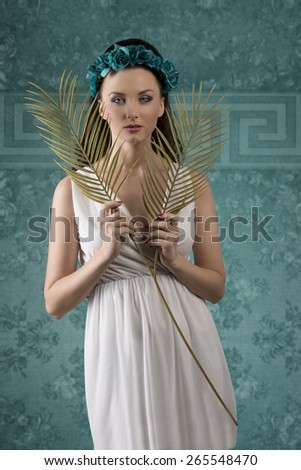 lovely brunette female with white dress and long hair posing in romantic spring portrait with floral crown and palm leafs in the hands  - stock photo
