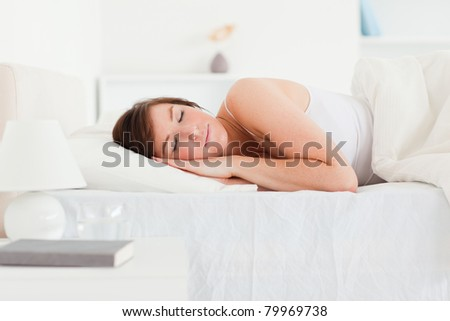 Lovely brunette woman having a rest while lying on a bed