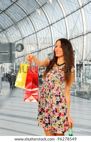lovely brunette woman in light dress with colorful shopping bags at the mall