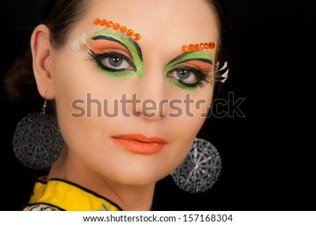 Lovely brunette woman portrait with creative make-up and orange spots - stock photo