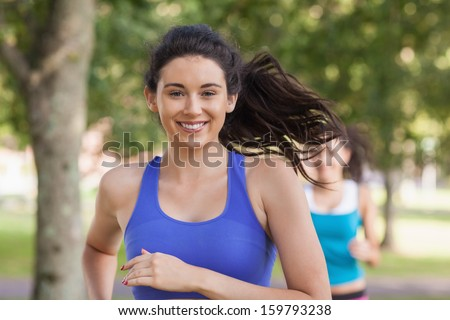 Lovely brunette woman running in a park smiling at camera - stock photo