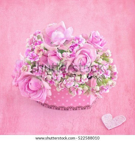 Lovely bunch of flowers .Beautiful fresh roses flowers in a box decorated with a heart on a pink background with texture .