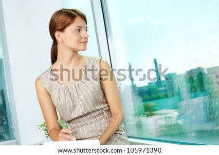 Lovely business lady taking a look at the urban landscape outside the window - stock photo