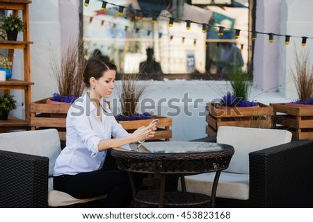 Lovely business woman with smile is sitting with touch pad in comfortable restaurant during recreation time, happy female student relaxes in coffee shop after university