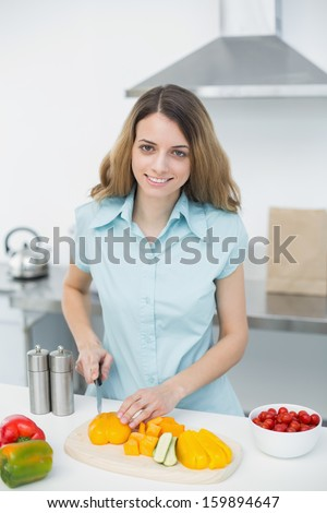 Lovely calm woman cutting vegetables smiling at camera standing in bright kitchen