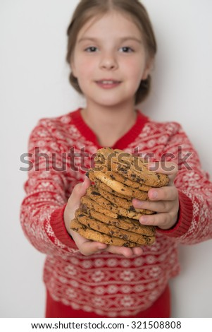 Lovely caucasian little girl wearing red christmas sweater holding cookies - stock photo