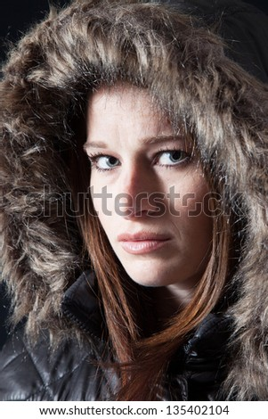 Lovely Caucasian woman in a heavy winter coat with a fur lined hood over her head, looking at the camera with a thoughtful expression